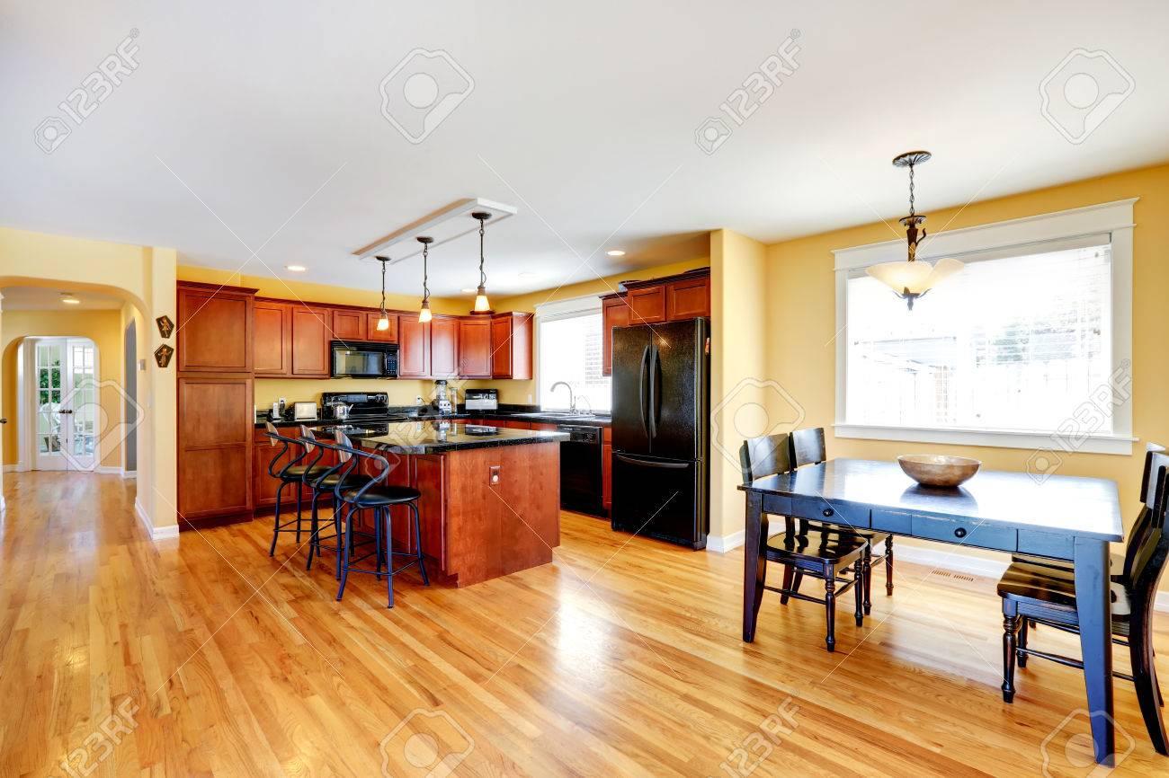 Amplia cocina con isla kithen y taburetes. Comedor con mesa rústica negro y  sillas