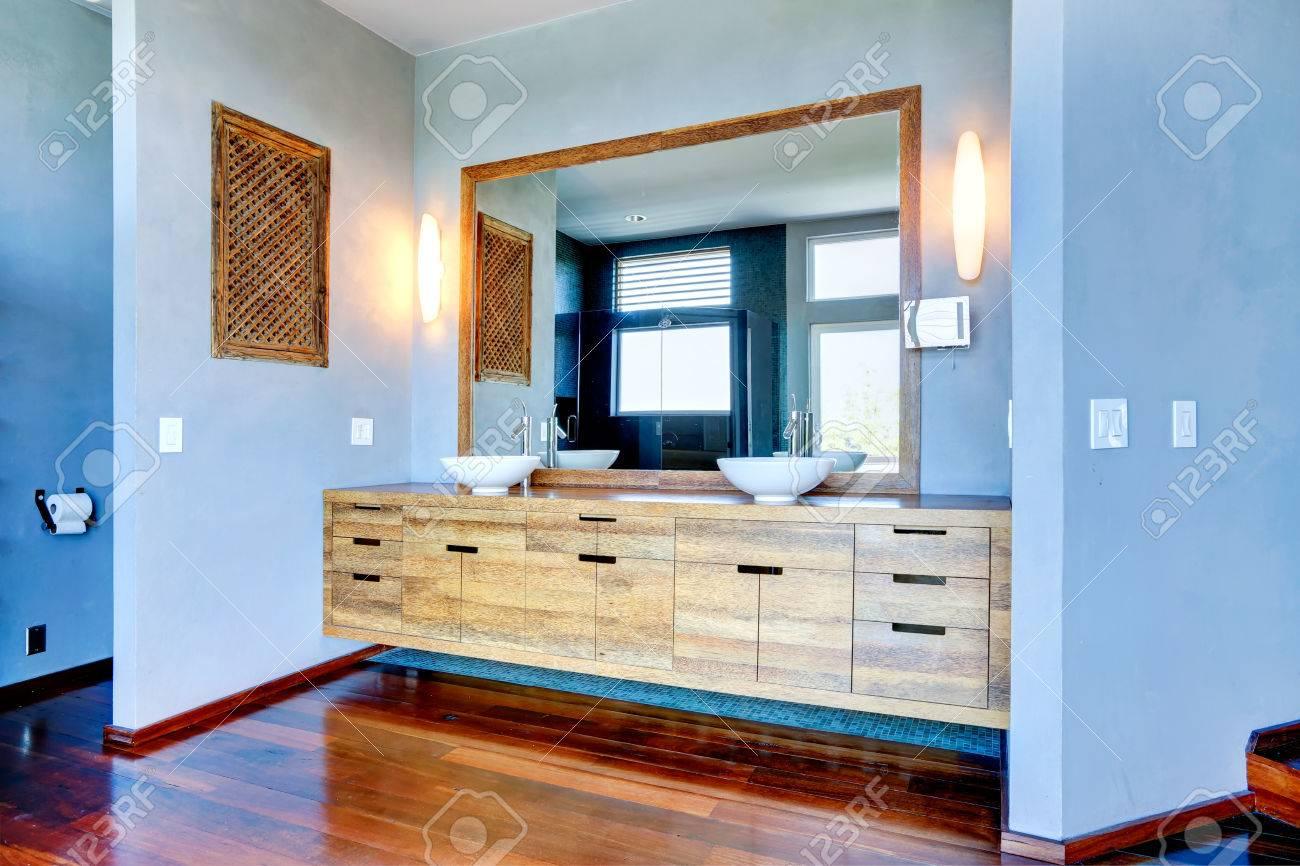 Intérieur de salle de bain bleu clair. Vue de l\'armoire en bois avec navire  coule et grand miroir