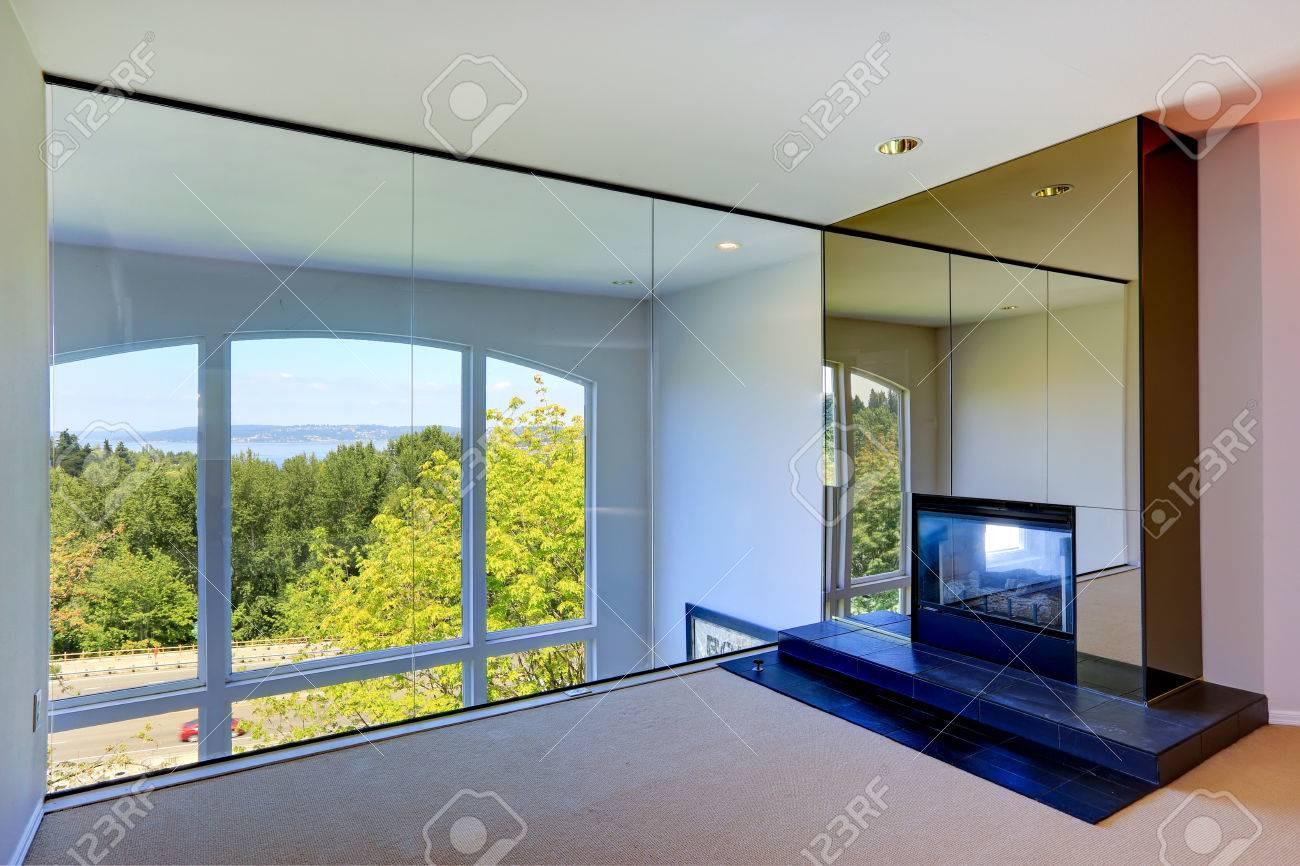 Stanza vuota luminosa con camino e parete di vetro che si affaccia ...