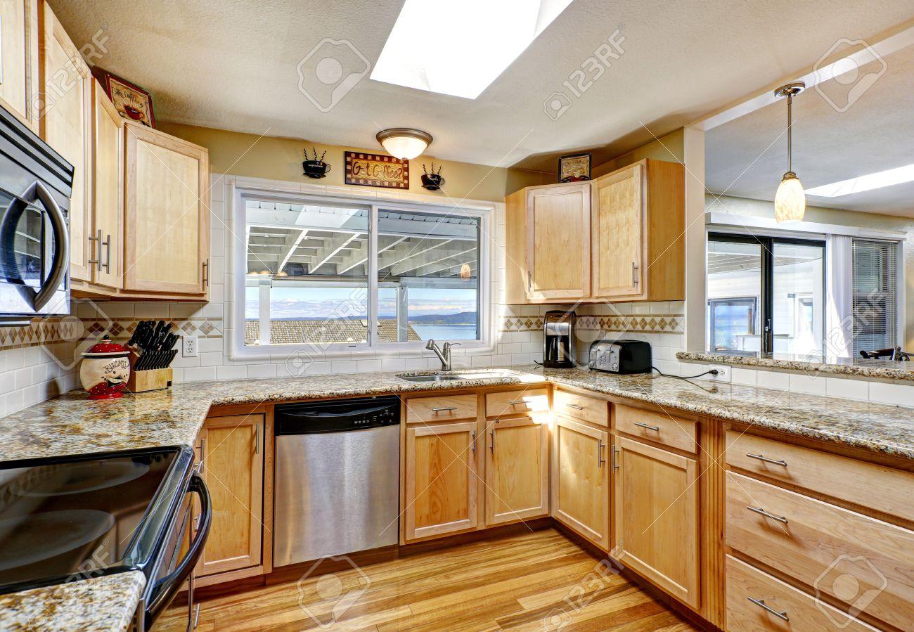 cocina luminosa con suelo de madera muebles de madera de tonos claros con encimeras de