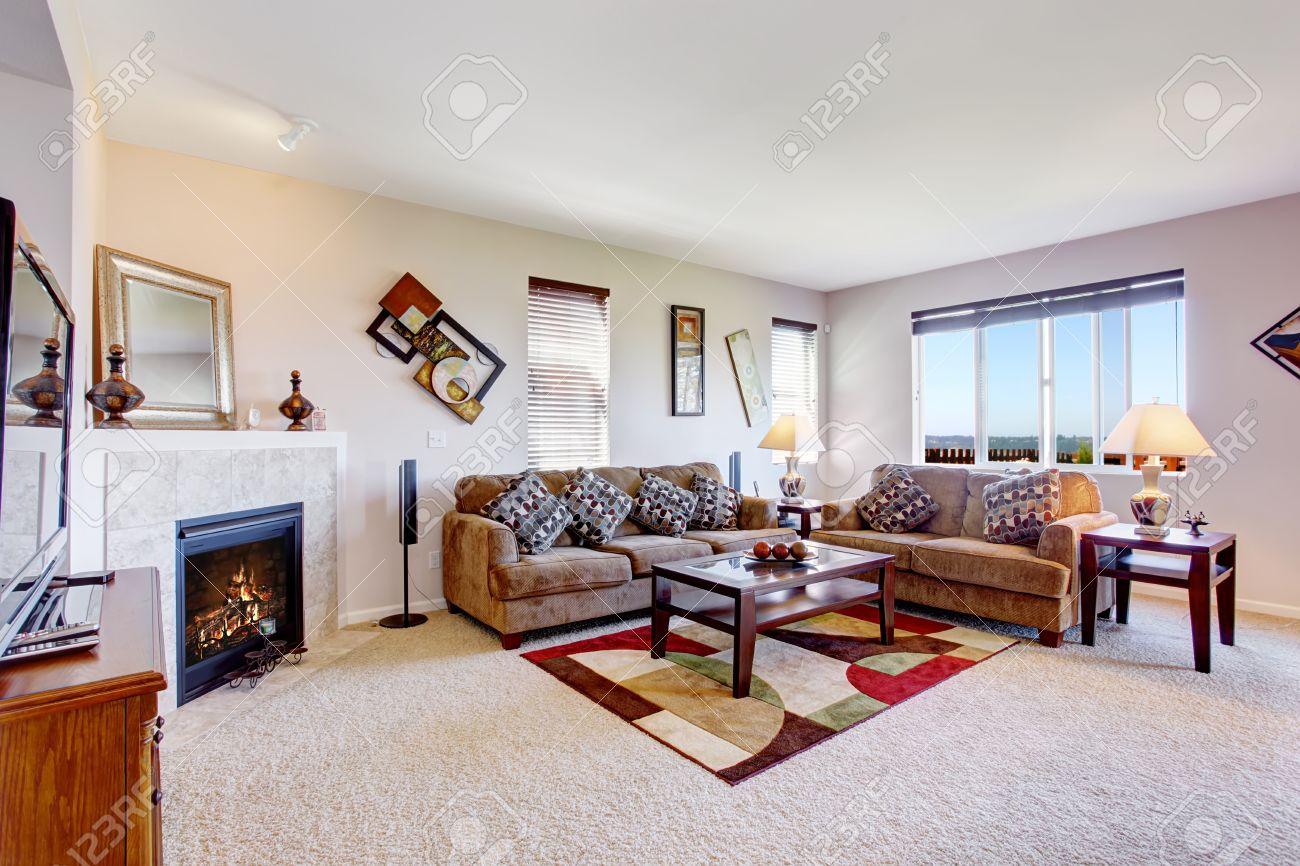Blanc salon avec cheminée et tapis coloré. Meublé avec des canapés marron  et une table basse