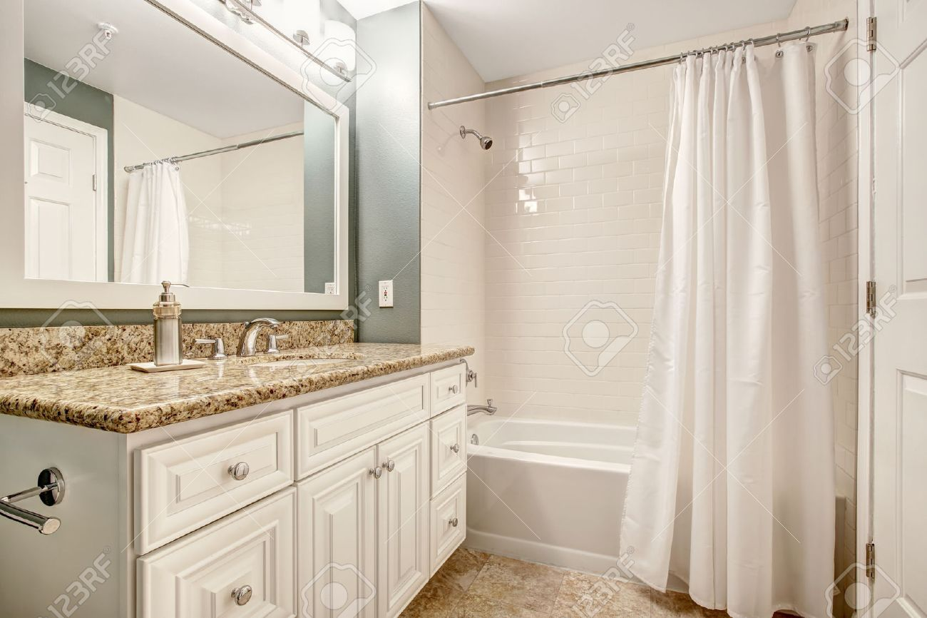 White bathroom vanity cabinet with granite top and mirror. Aqua..