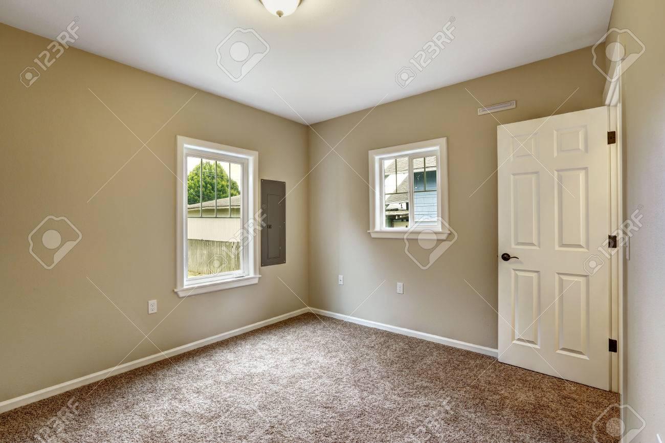 Bedroom With Beige Walls, Soft Brown Carpet Floor And Windows Stock