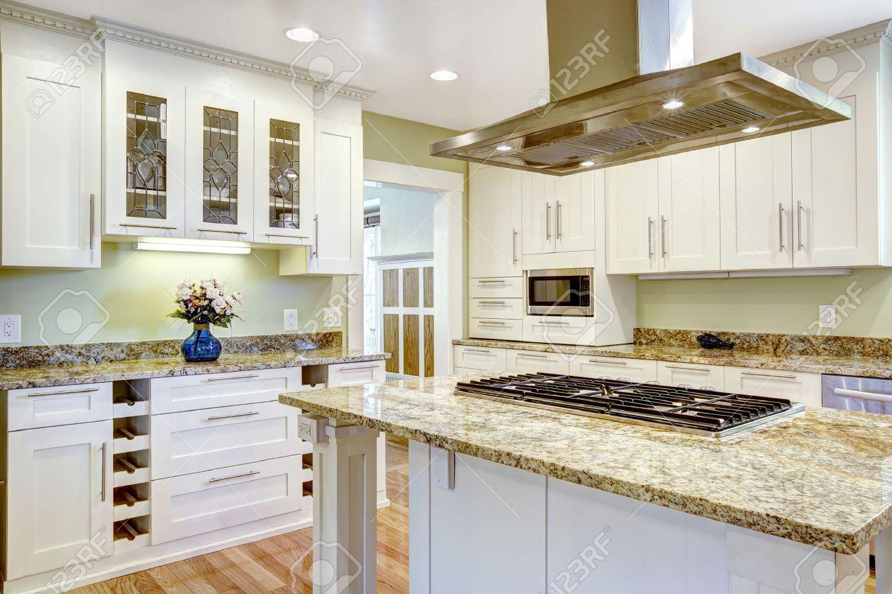Diseño de cocina moderna y práctica. Mueble blanco con encimera de granito,  isla de cocina con una función de estufa y campana de acero