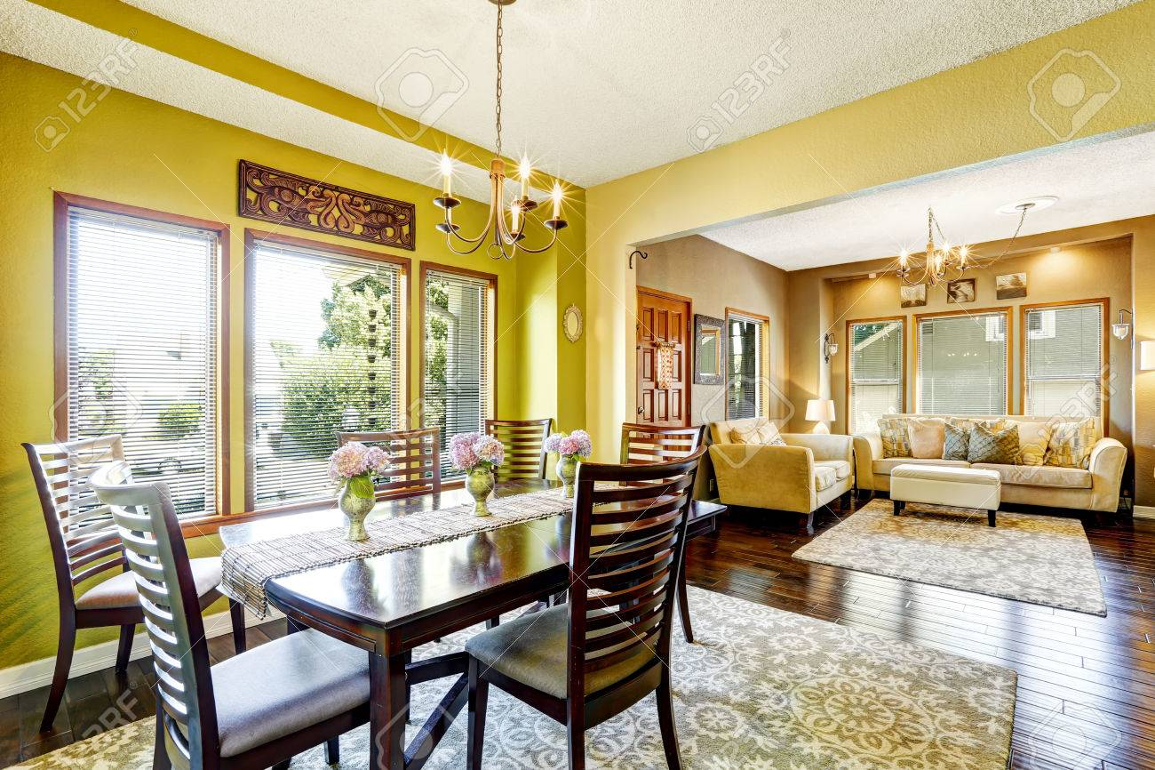 House with open floor plan. Bright yellow dininig room with wooden..