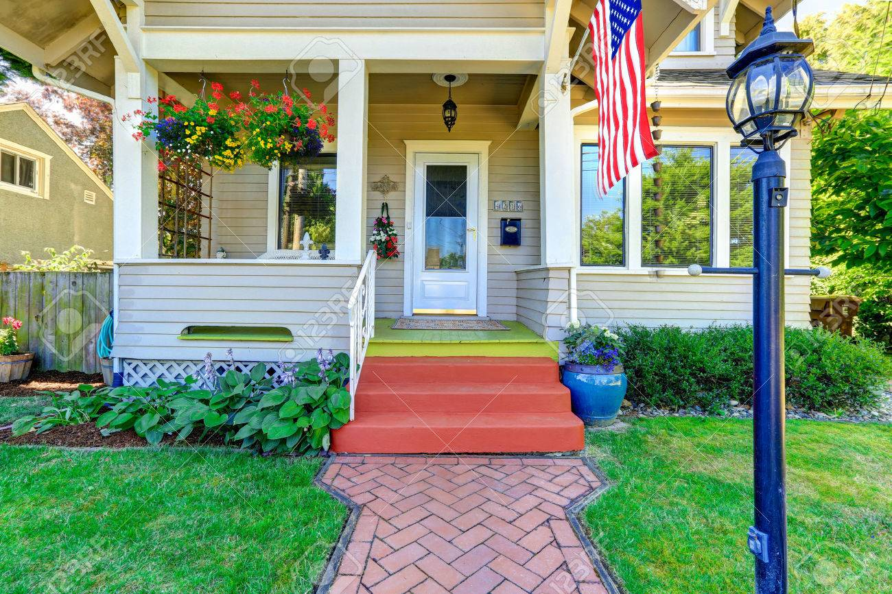 Classic American House Entrance Porch, Decorated With Hanging Flower Pots.  Tile Brick Walkway Stock