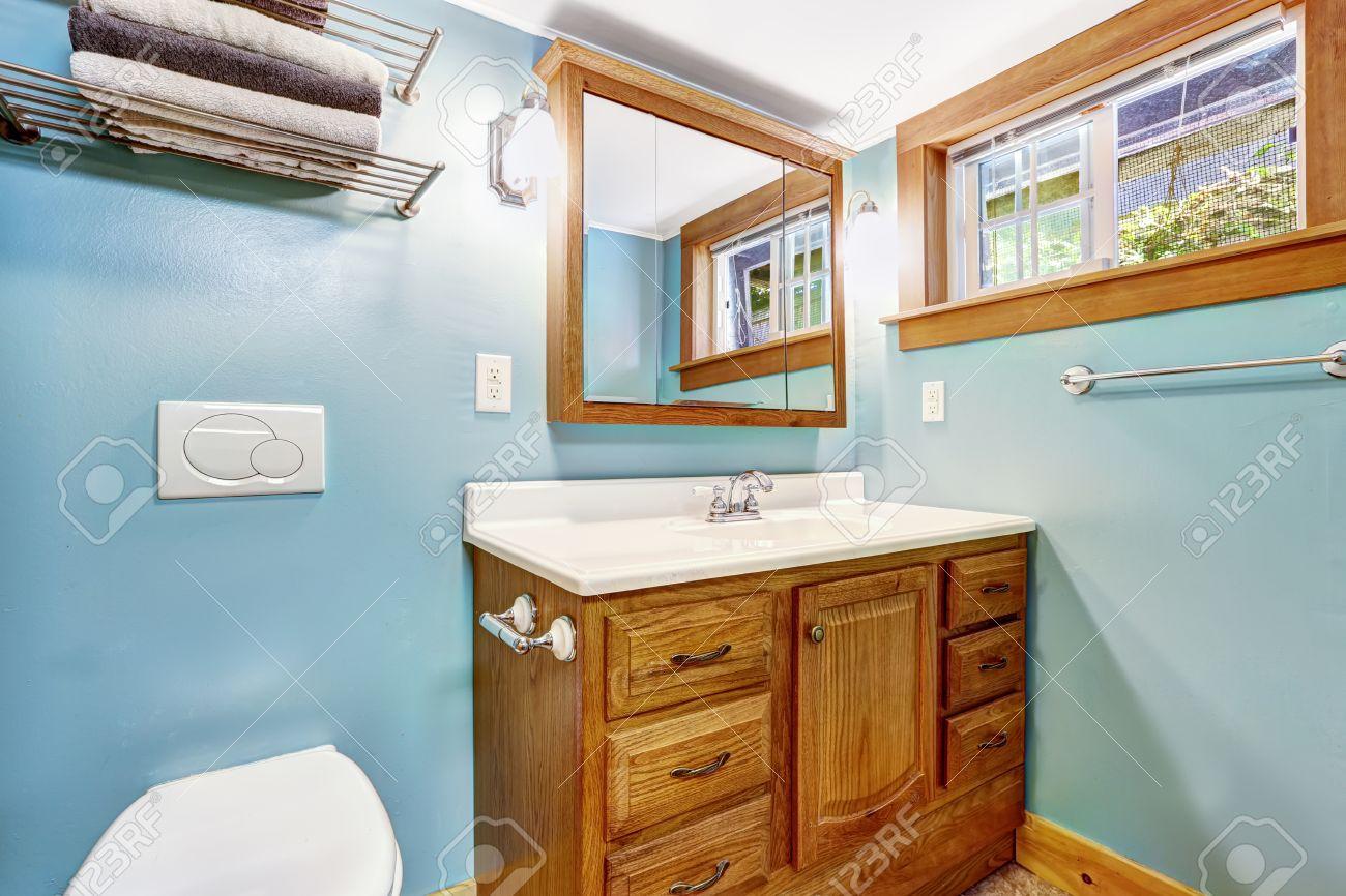 Intérieur de salle de bain bleu avec meuble de rangement en bois et fenêtre  boiseries