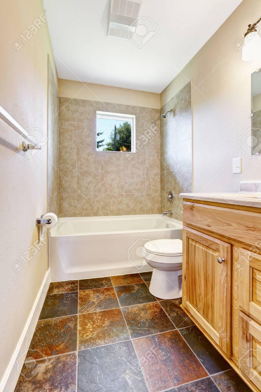 Tom badrum med kakel vägg trim, litet fönster och trä fåfänga skåp ...