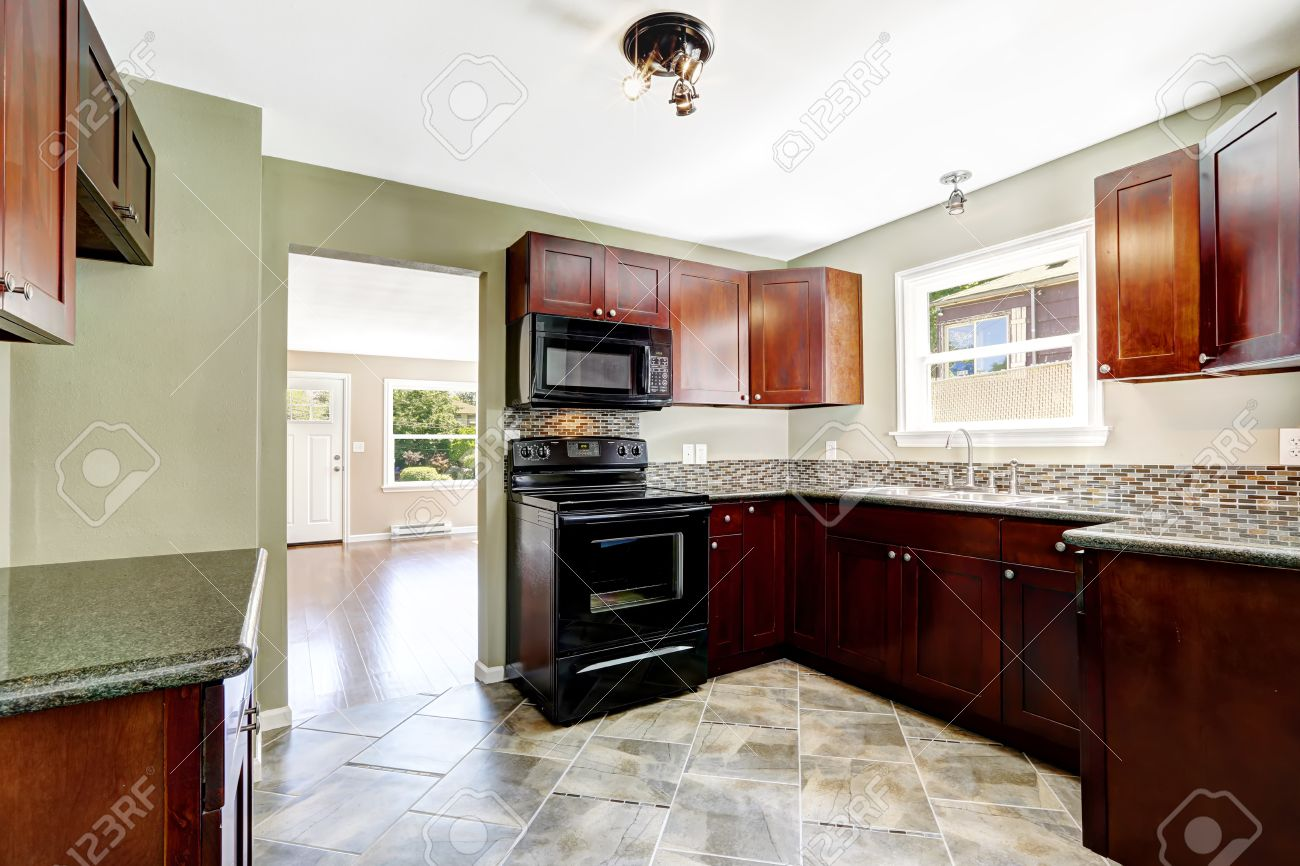 Great Kitchen With Bright Burgundy Cabinets And Black Appliances. Light Mint  Walls And Tile Floor Stock