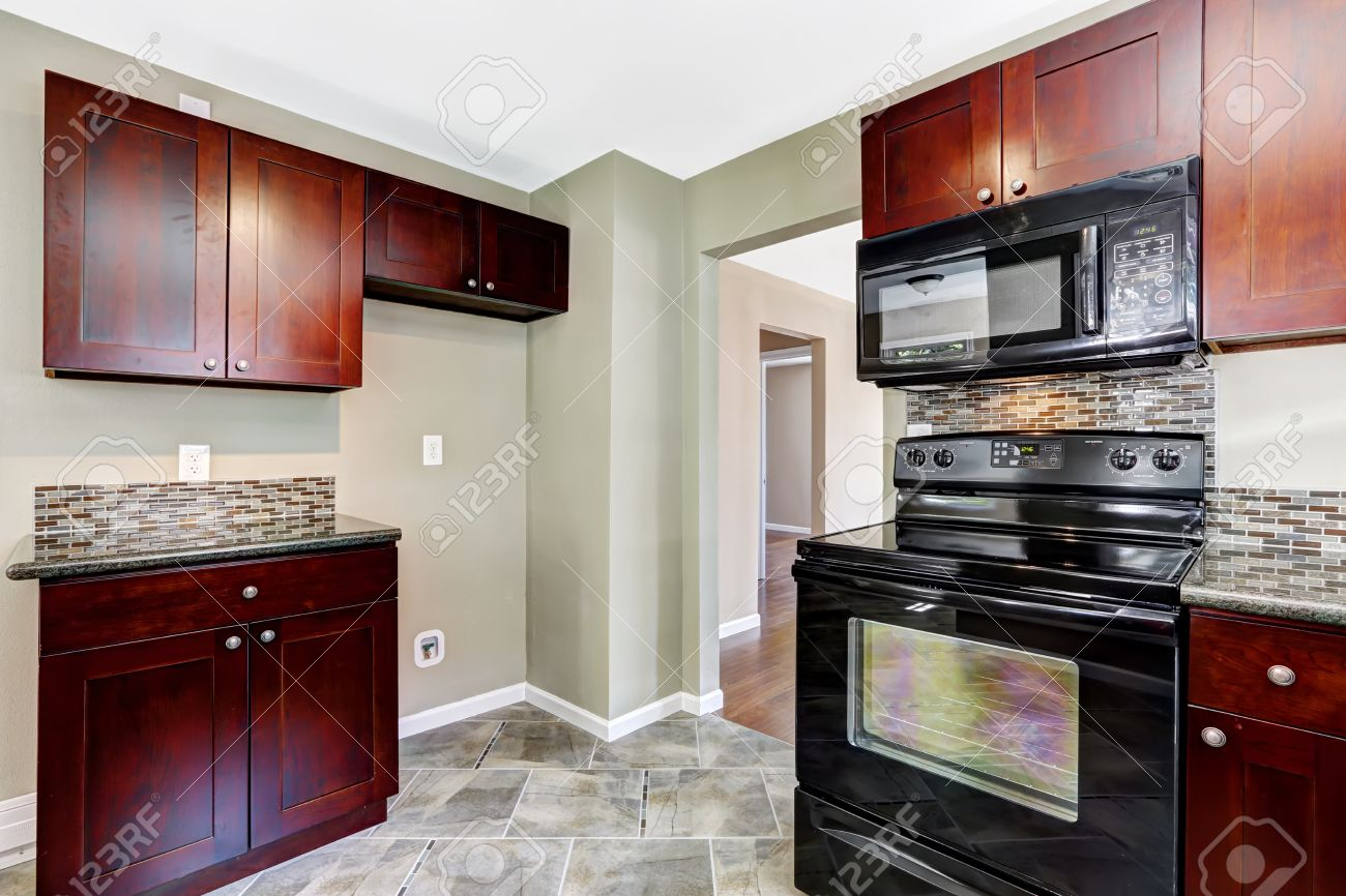Kitchen With Bright Burgundy Cabinets And Black Appliances. Light Mint  Walls And Tile Floor Stock