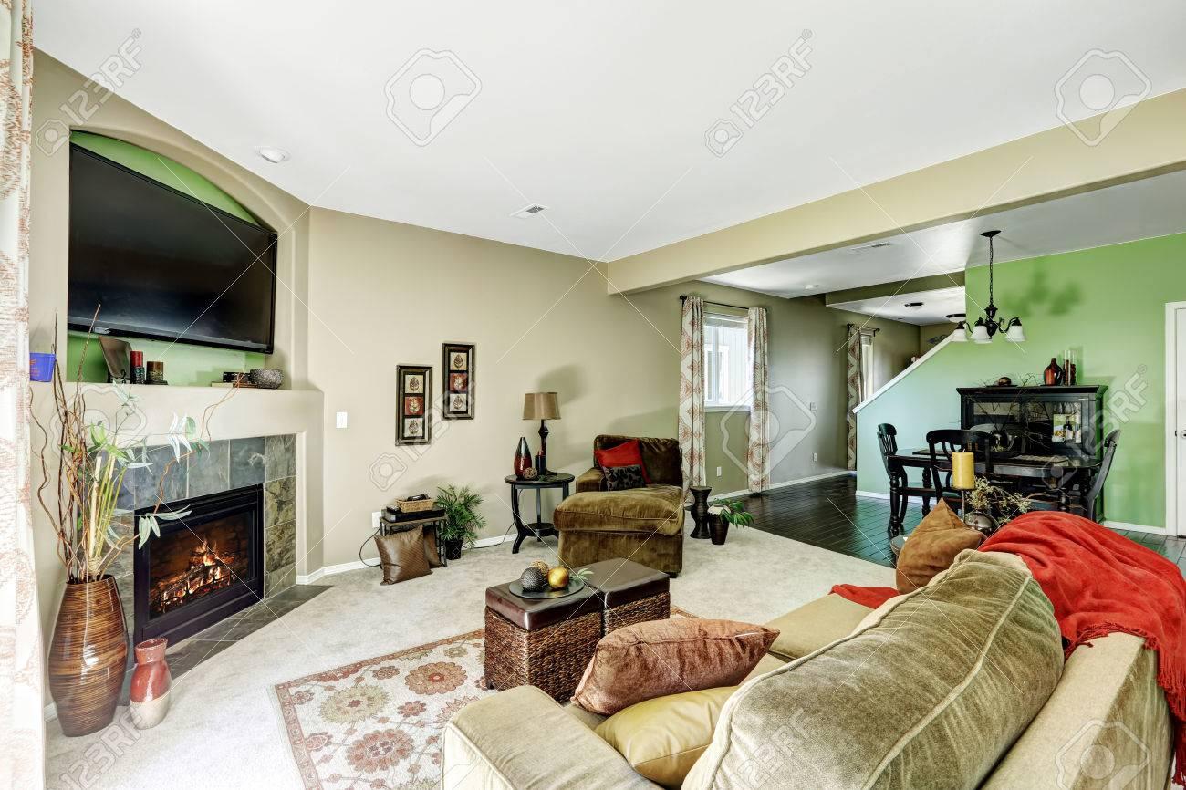 Soggiorno con pareti beige e verdi con caminetto e comodo divano