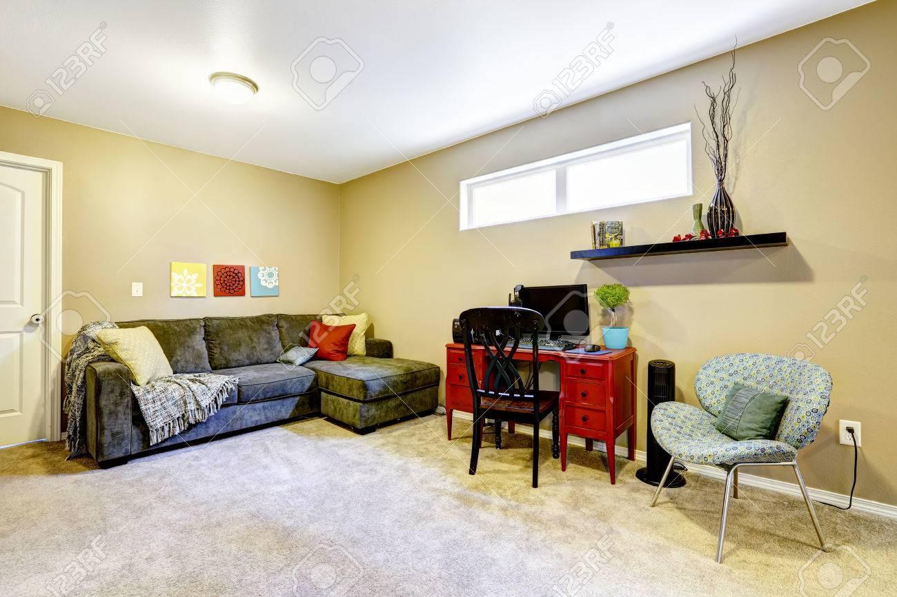 Salle de sous sol avec un canapé confortable et dun bureau en bois