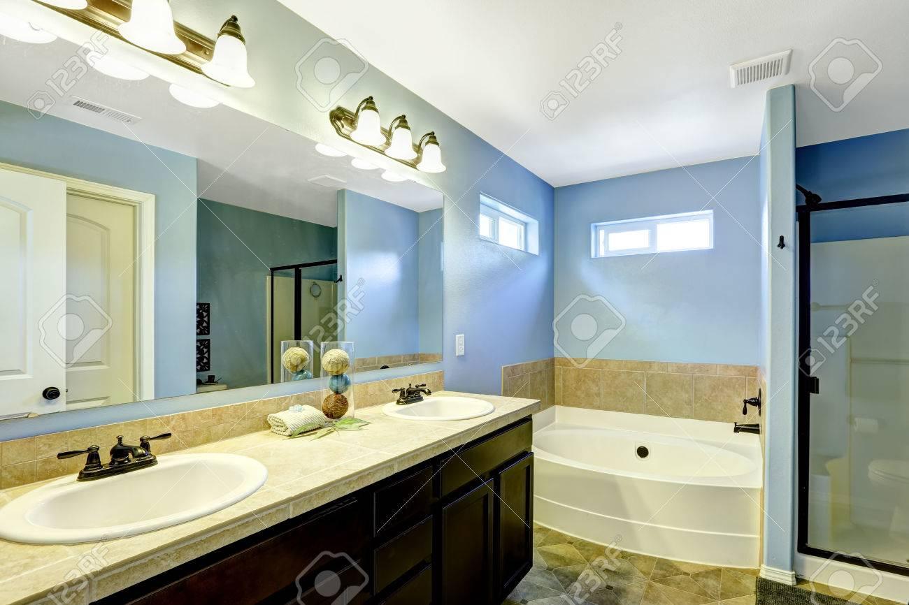 Blauwe badkamer met houten kast spiegel en tegel bekleding