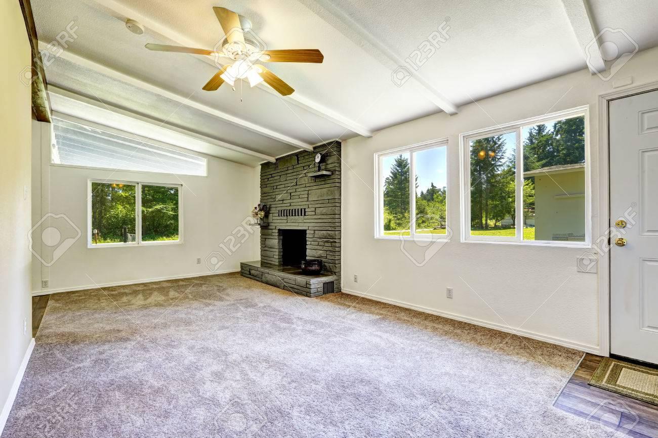 Lumineux salon vide avec cheminée et de la moquette. Ancien intérieur de la  maison