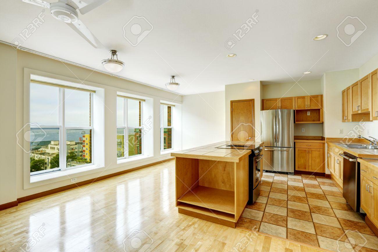 Empty Studio Open Floor Plan Living Room With Large Windows And Kitchen Area