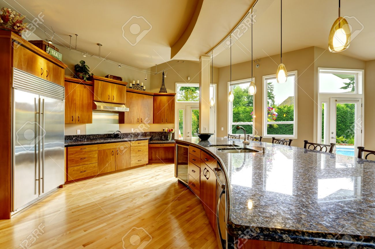 Spacious Luxury Kitchen Room With Round Kitchen Island And Black Granite  Tops Stock Photo   31387263
