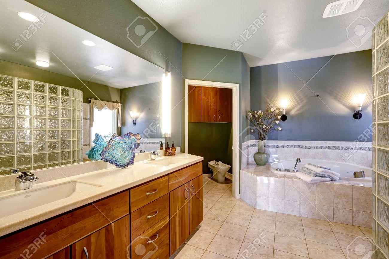 Geräumiges Badezimmer Mit Dunkelgrünen Wänden Und Beige Fliesen. Braun  Waschbeckenunterschrank Mit Großem Spiegel Und Whirlpool