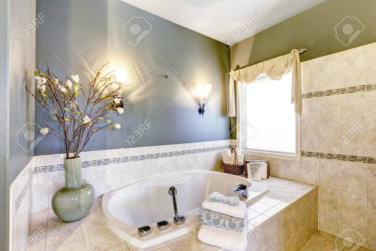 Bathroom With Bath Tub Tile Trim And Contrast Green Lavender Walls Stock Photo