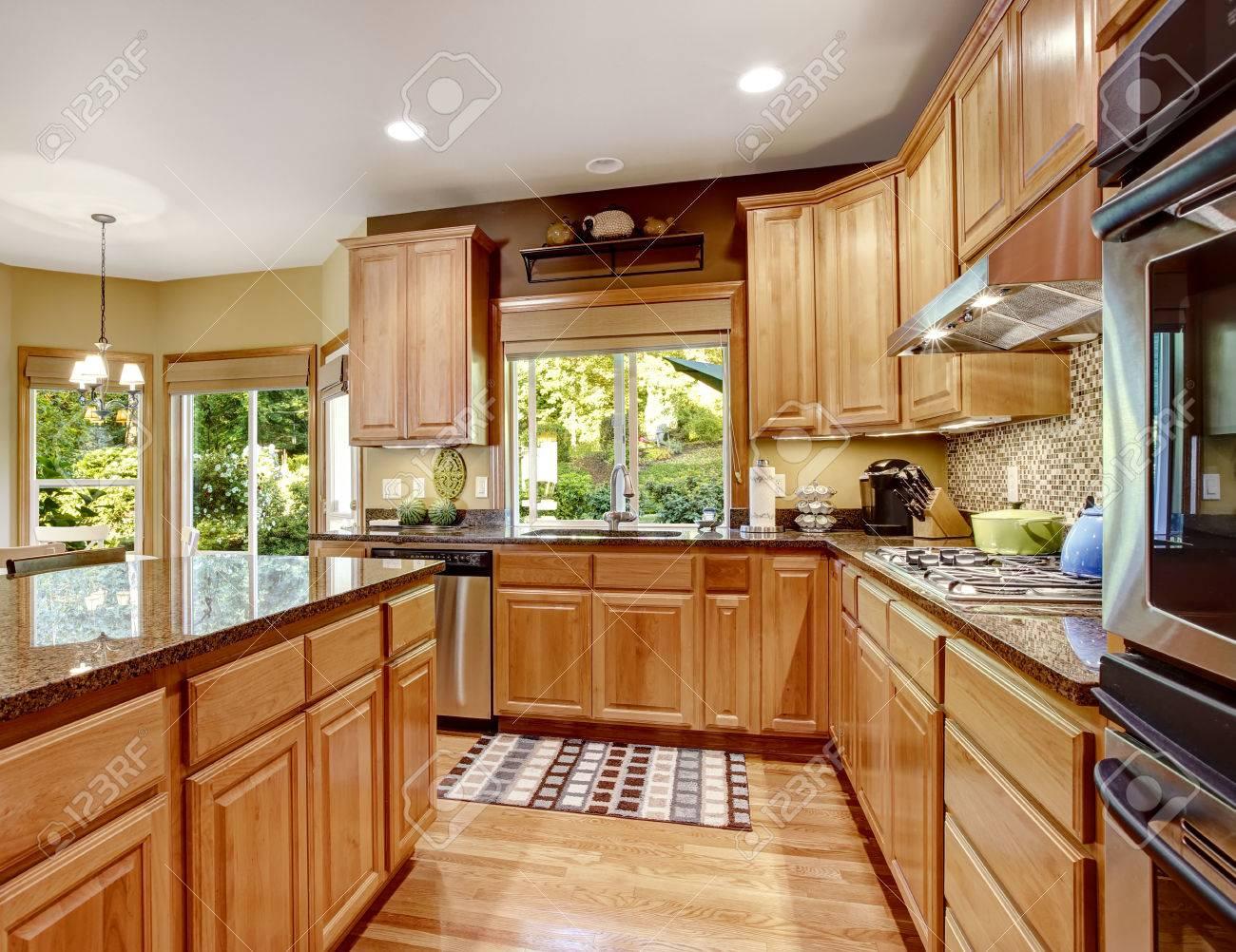 Cuisine Carreaux dedans lumière salle de cuisine brun avec des sommets de granit et îlot de