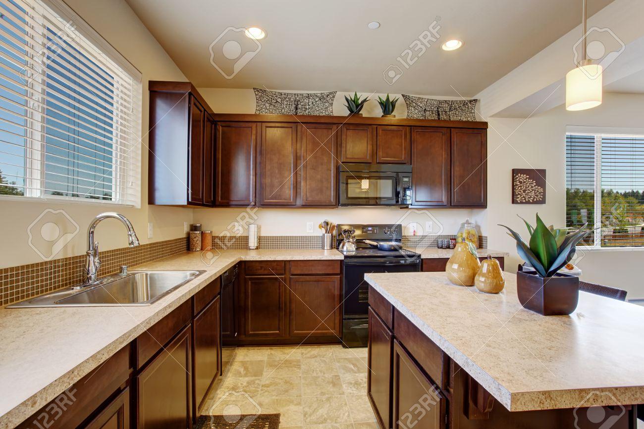 Camera Cucina moderna con isola cucina e sgabelli. Armadi marrone scuro,  elettrodomestici in acciaio e pavimento di piastrelle