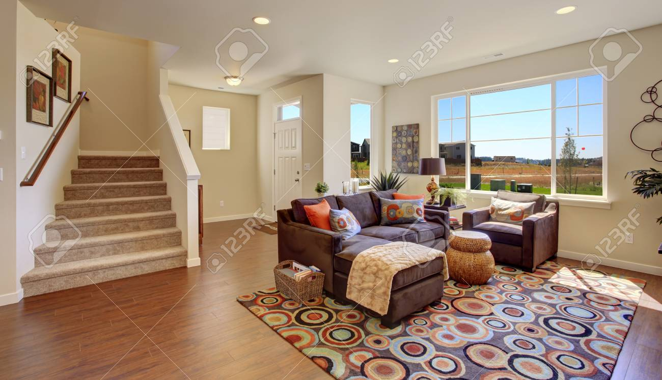 Ivory living room with hardwood floor. Brown couch, colorful..