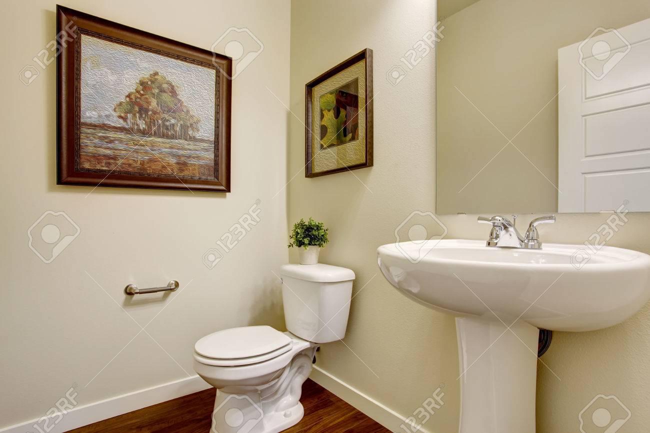 weicher elfenbein badezimmer mit holzboden, weiße toilette