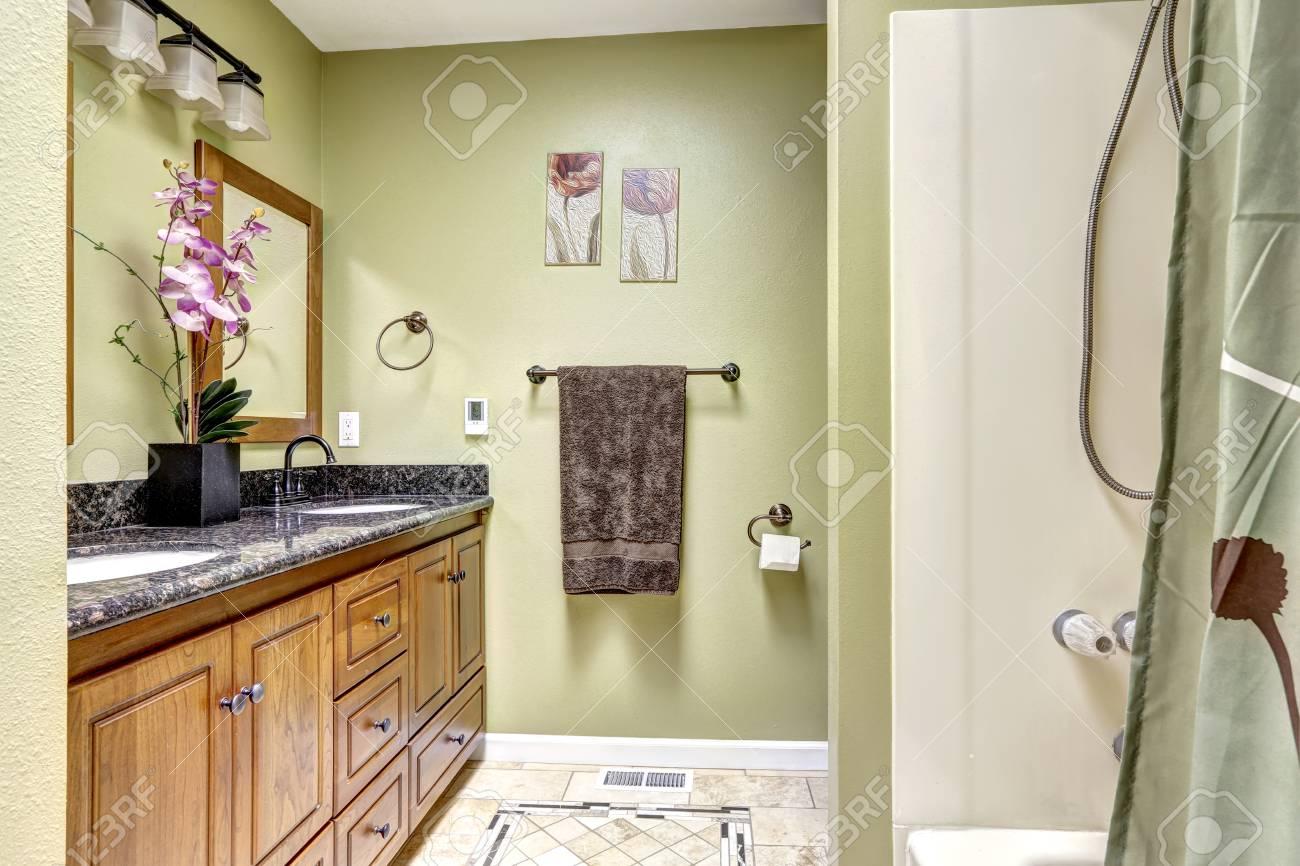 Salle de bains lumineuse dans ton vert clair. Cabinet en bois avec comptoir  en granit orné de fleurs.
