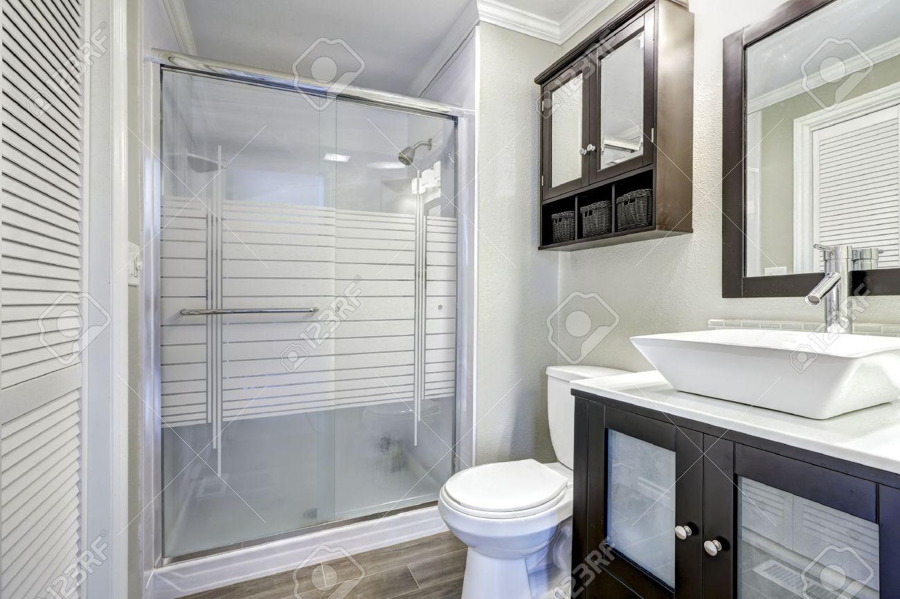 Intérieur de salle de bains moderne avec porte de douche en verre. Meuble  de rangement Brown avec blanc vasque et miroir