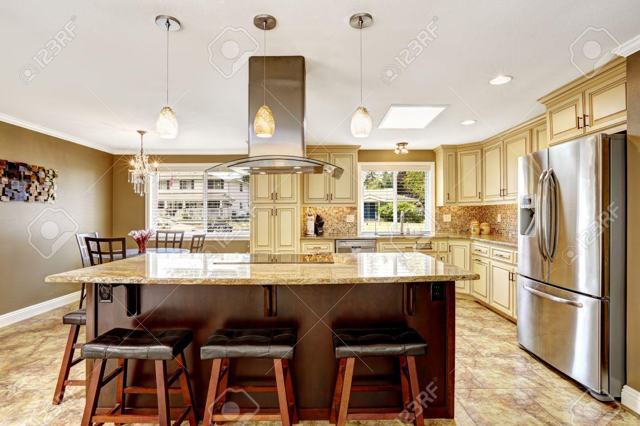 grande cucina ad isola con piano cottura da incasso top in granito e cappa in acciaio
