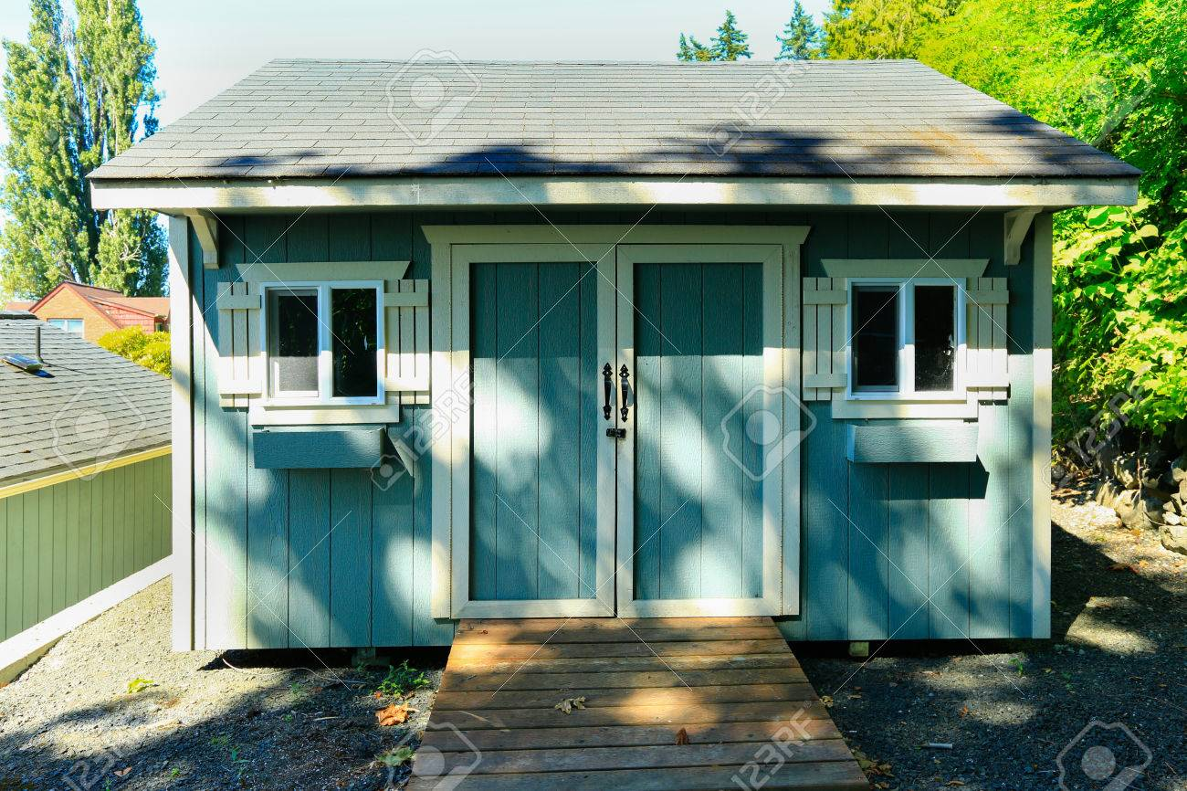 Wooden Shed With Small Windows And White Trim