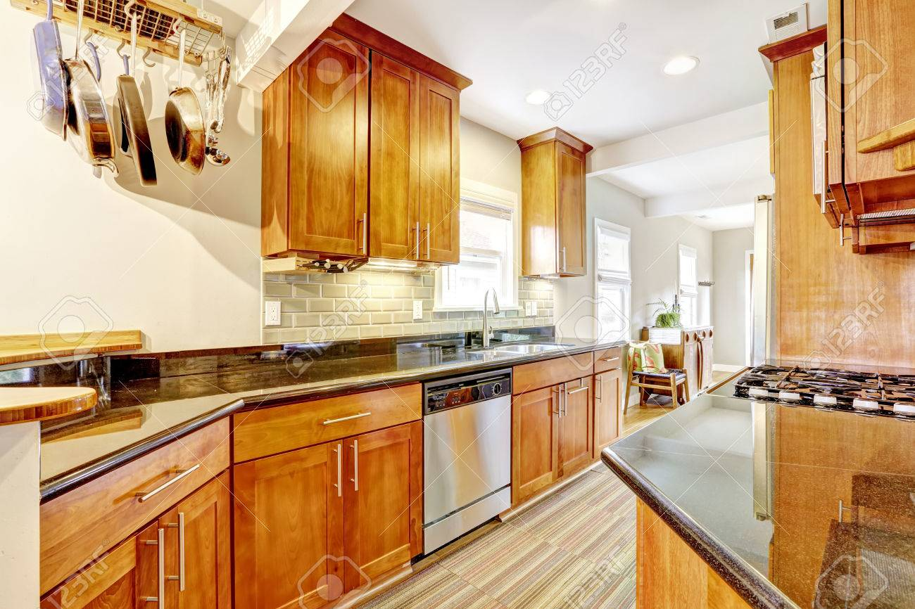 Cocina brillante marrón gabinetes con topes en granito negro sala cocina con teja vuelta ajuste