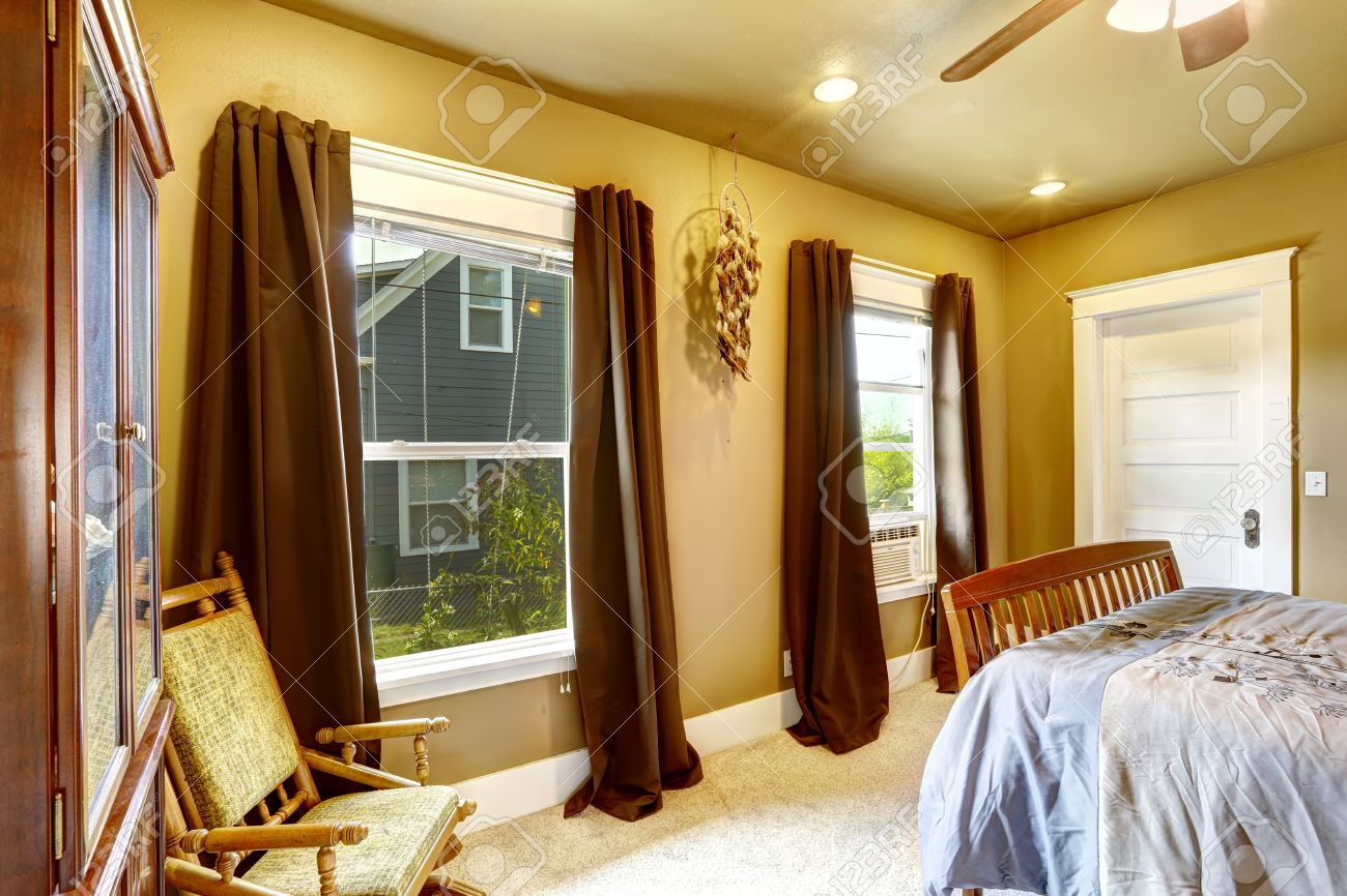 Brown and yellow bedroom - Stock Photo Warm Tones Bedroom With Light Yellow Walls And Brown Curtains
