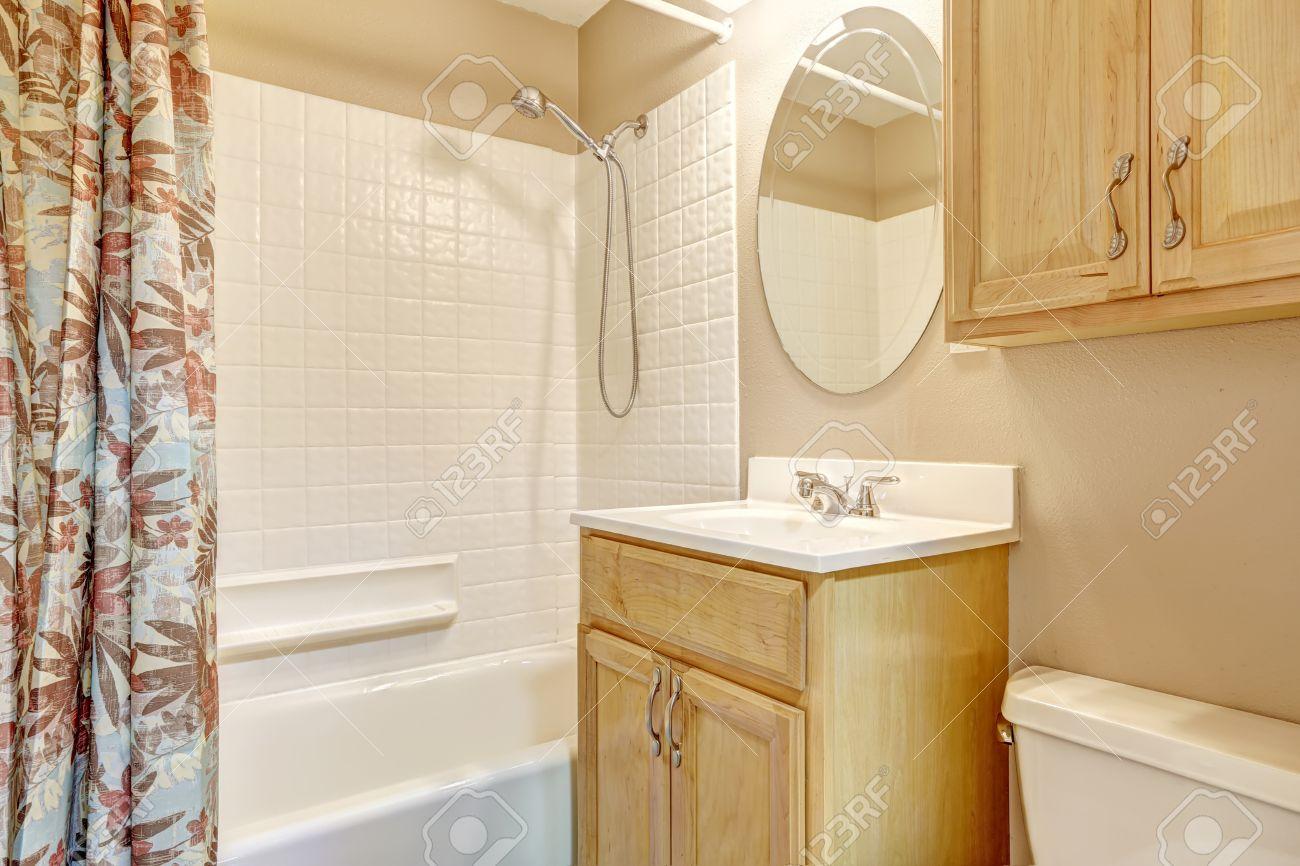 luce del bagno beige con armadi in legno e tenda floreale. bianco ... - Luce Vasca Da Bagno