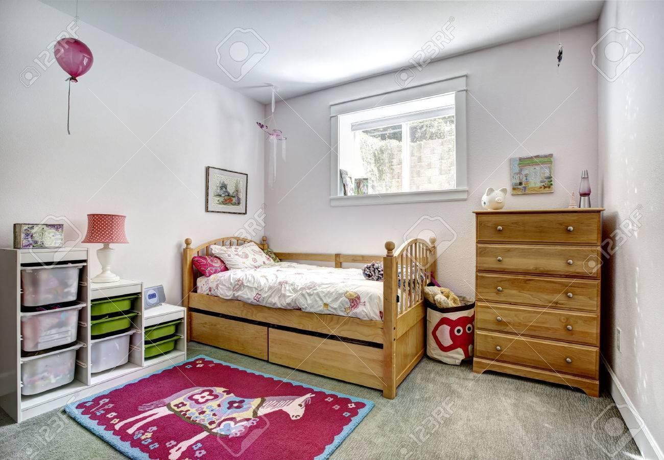 素朴なベッドやドレッサーと居心地の良い子供部屋。カーペットの床で陽気