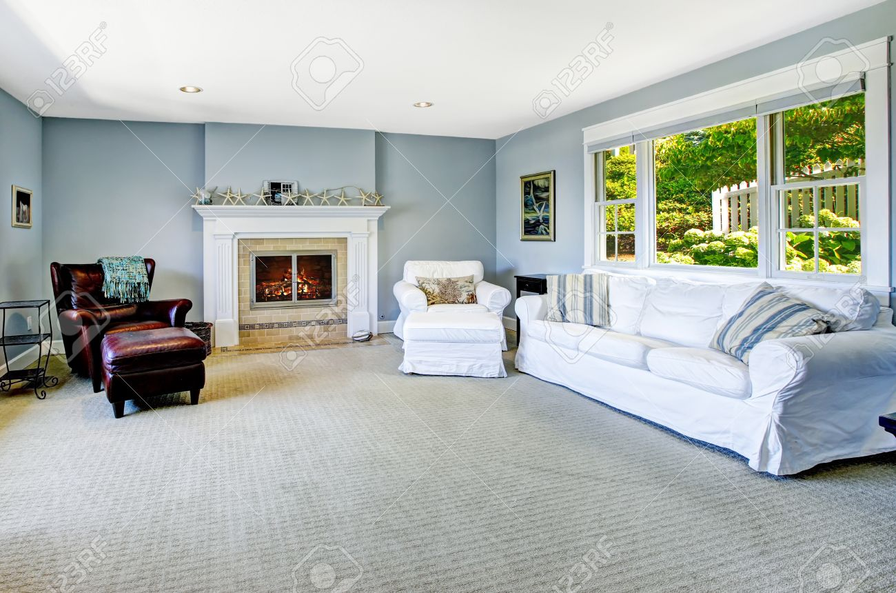 Light blue living room with white sofa, armchair and leather..