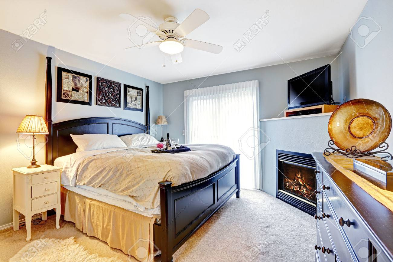 Light Blue Master Bedroom With Queen Size Bed, Dresser. Room Has Fireplace  And TV