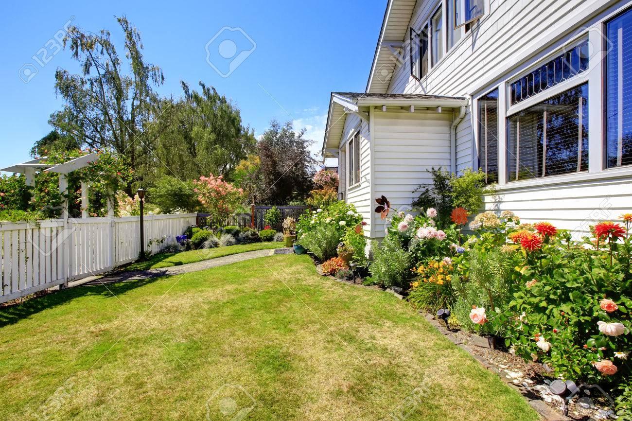 vorgarten landschaft mit blumen und weißen zaun lizenzfreie fotos