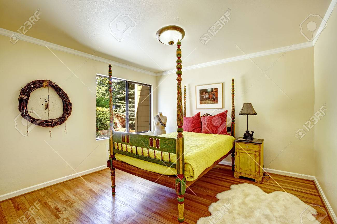 Colorful Carved Wood Bed With High Poles And Yellow Bedding... Stock ...