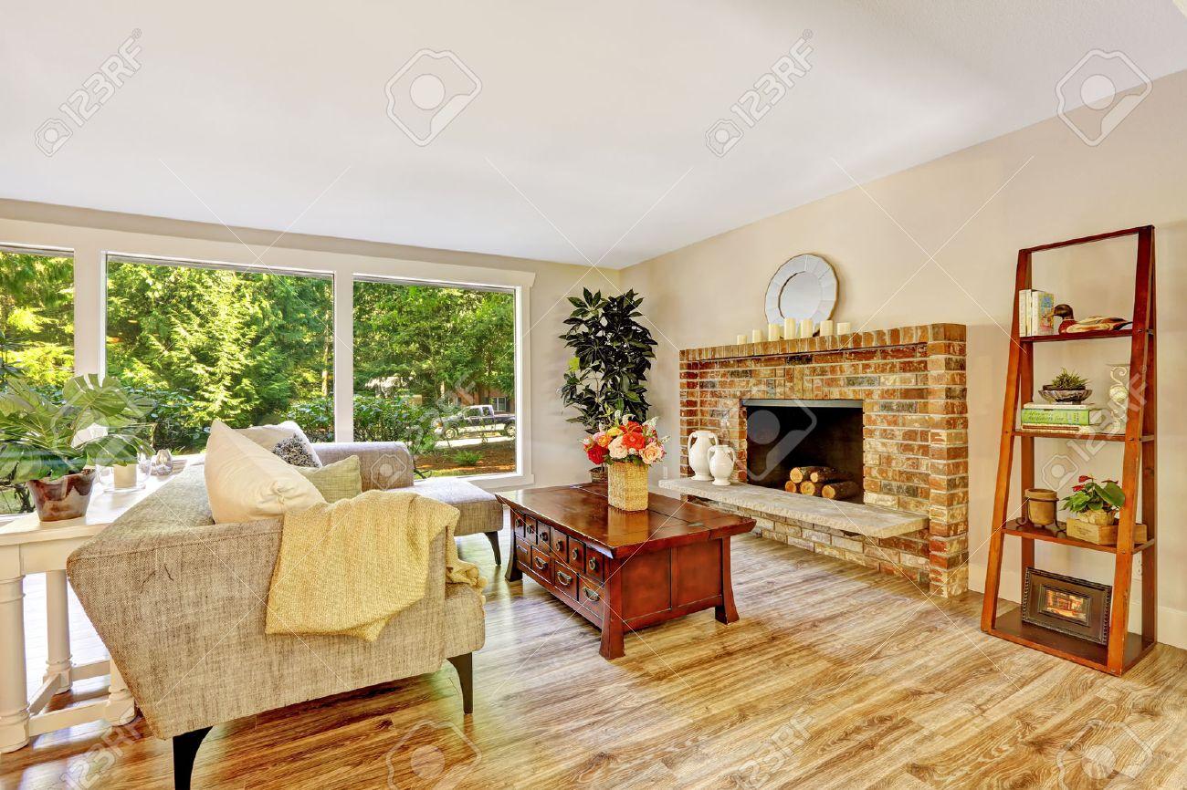 Ruime lichte woonkamer met stenen open haard, bank, houten ...