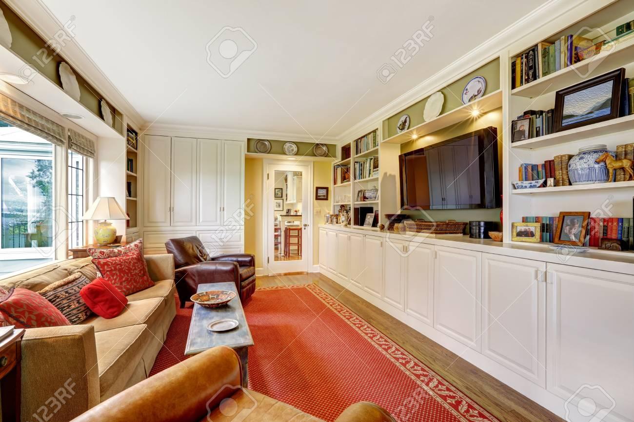 Soggiorno con armadi bianchi, tv, mobili marroni e tappeto rosso