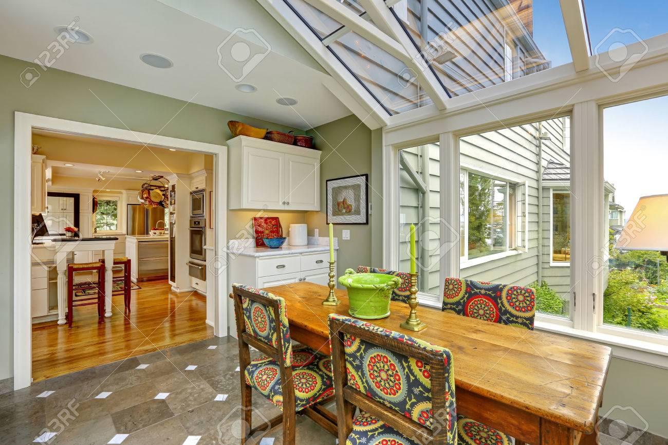 Véranda patio avec plafond voûté transparent, table à manger en bois avec des chaises colorées