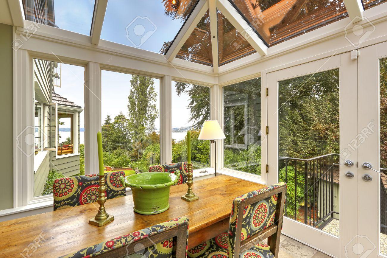 Véranda patio avec plafond voûté transparent, table à manger en bois avec des chaises colorées. Sortie à la cour