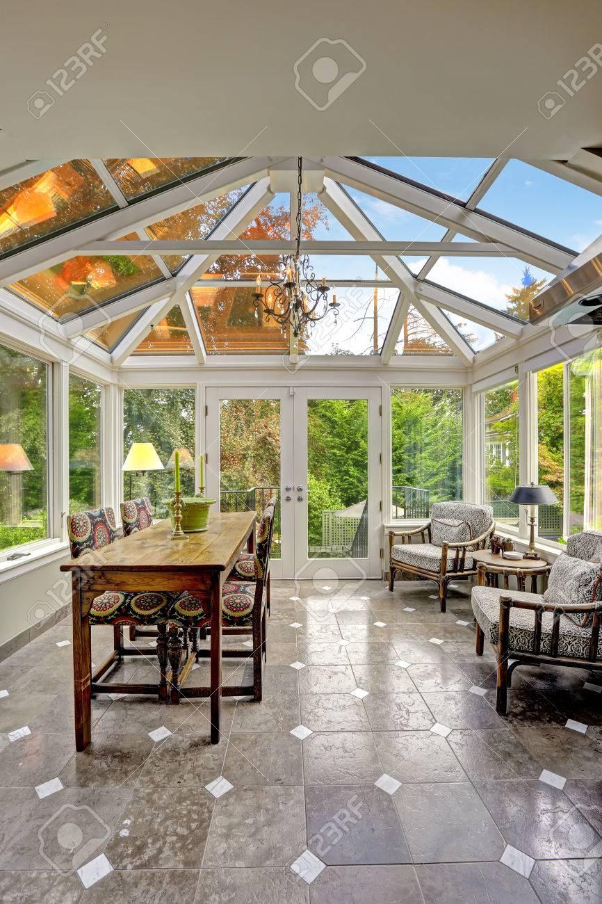 Véranda patio avec plafond voûté transparent, table de salle à manger ensemble avec coin salon