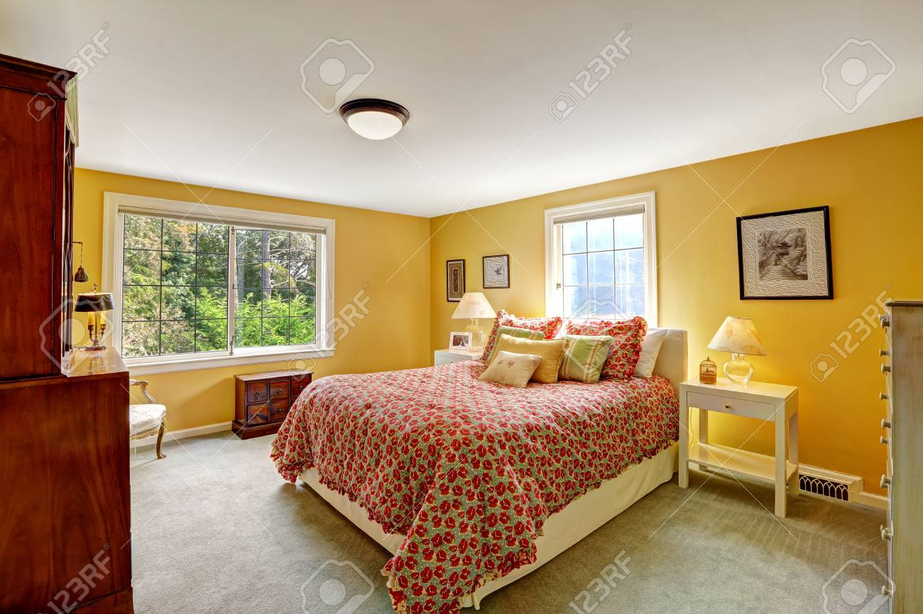 Cheerful Bedroom Interior In Bright Yellow Color And Red Bedding