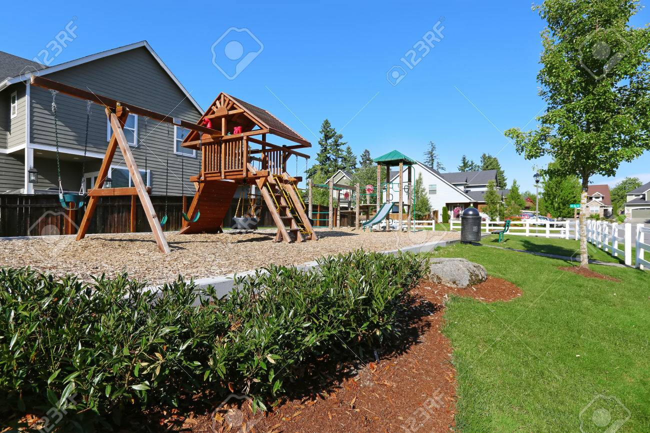 playground in american neighborhood with swings slids and playhouse