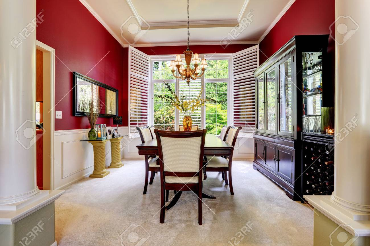 luxury dining room with bright red wall and white french window