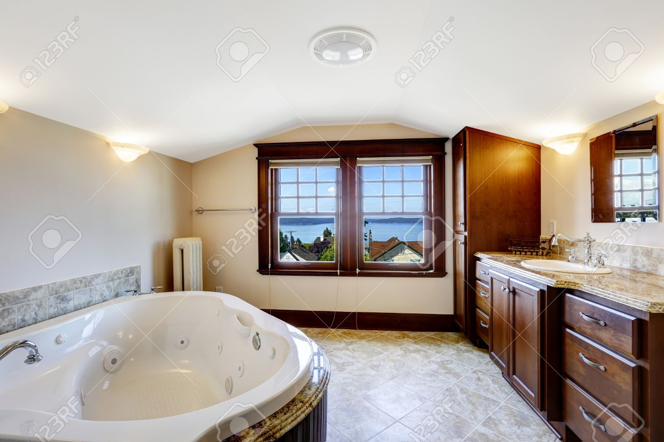 Luxury bathroom with whirlpool, brown cabinet and white whirlpool..