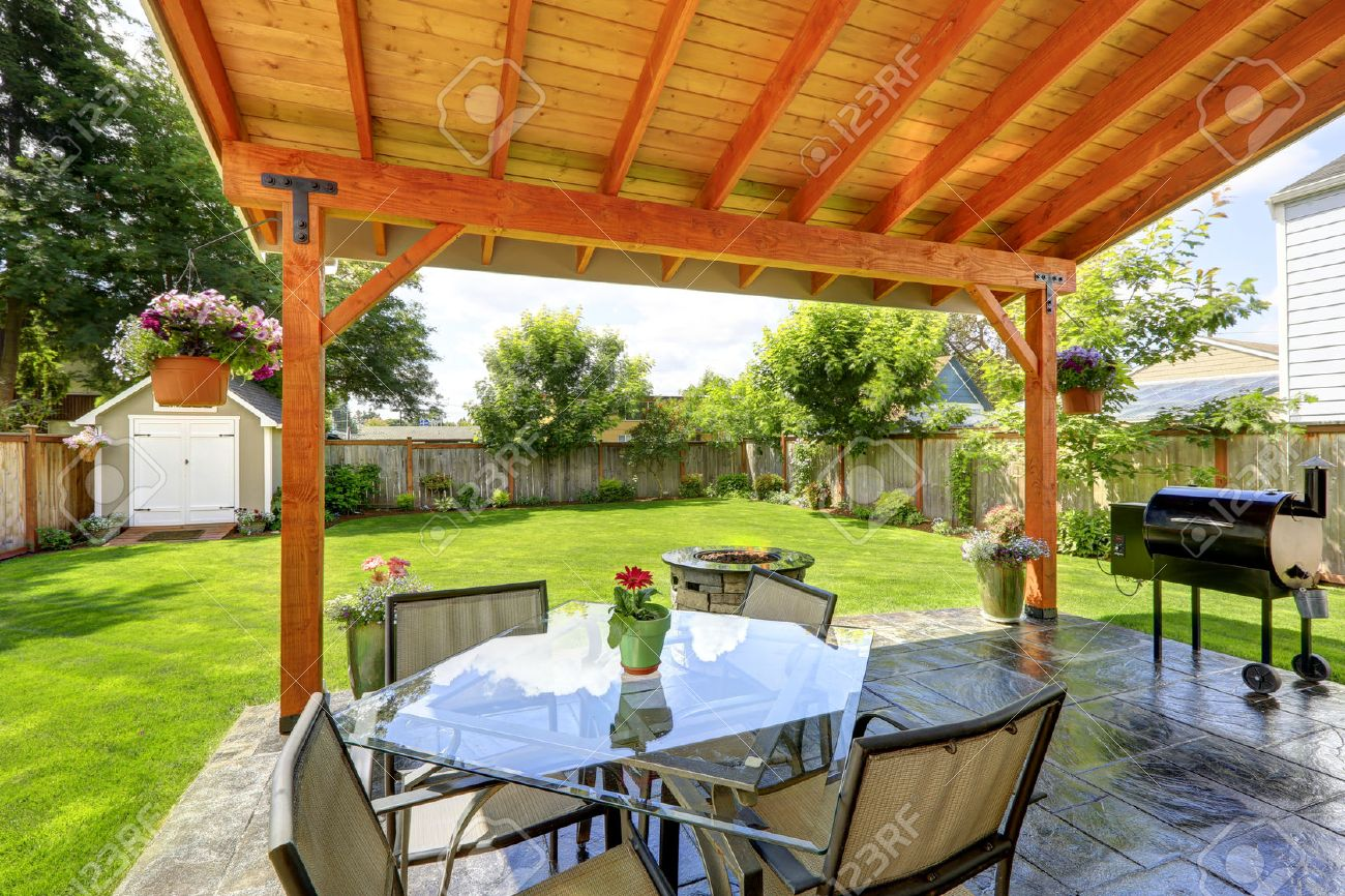 Pergola With Patio Area. Glass Top Table With Chairs, Fire Pit And Barbecue  Stock