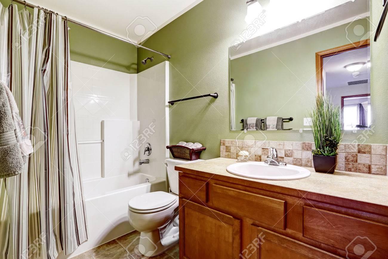 Bathroom interior en vert avec blanc baignoire et meuble en bois avec  carreaux de faïence