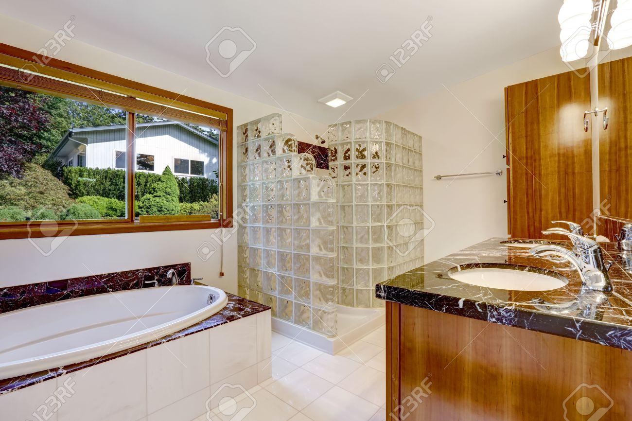 Badezimmer Mit Glasblock Abgeschirmt Dusche. Brown Schrank Mit Schwarzem  Granit Top Und Weiße Badewanne Mit